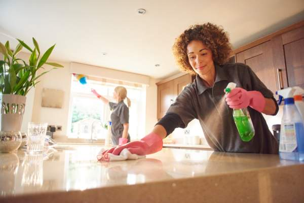 two professional cleaners in a domestic kitchen spraying cleaner onto a granite work surface