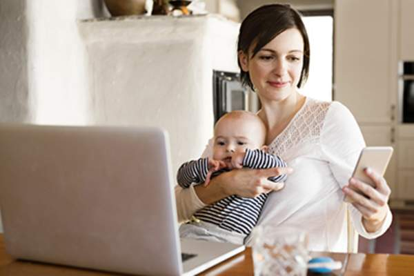 Mother at home with baby working on laptop and looking at smartphone.