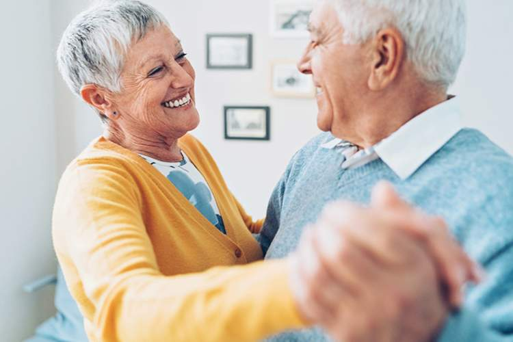 Smiling senior couple dancing at home.