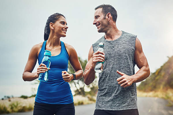 Couple jogging with water bottles.