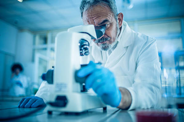 Scientist looking through a microscope.