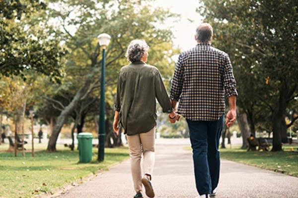 Senior couple walking through a park holding hands.