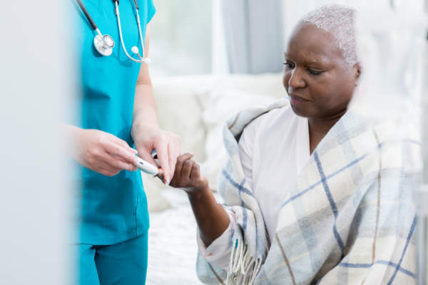 Home healthcare nurse checks patient's blood sugar