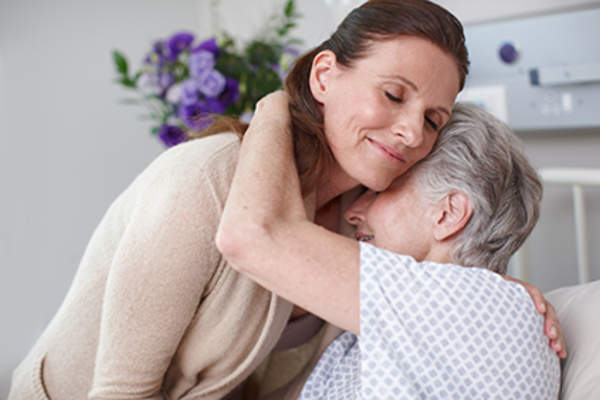 Caregiver hugging senior mother.
