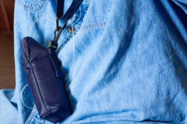 Man wearing blue shirt with chemo infuser bag.