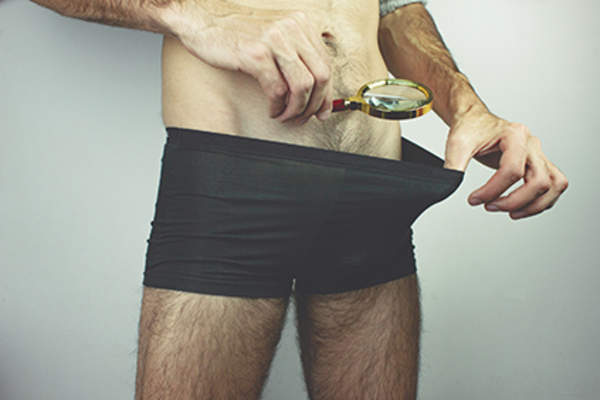 Man looking inside his underwear with a magnifying glass.