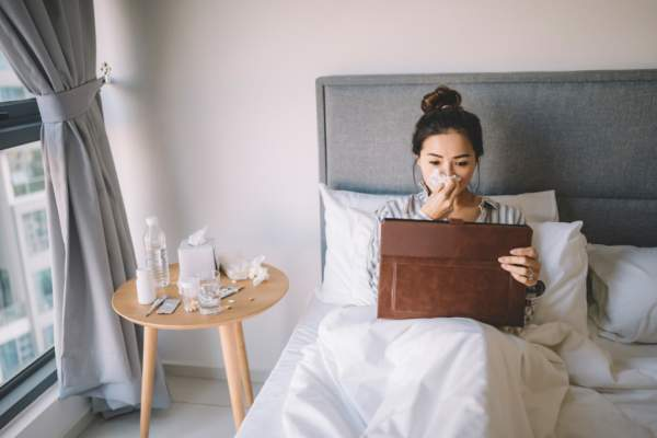 young woman sick in bed looking at tablet