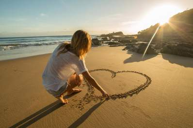 Young woman drawing a heart on beach sand in the sunshine.
