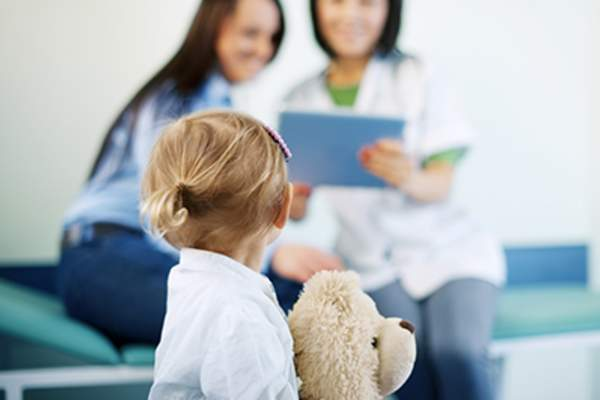 Young girl holding teddy bear at doctor visit.