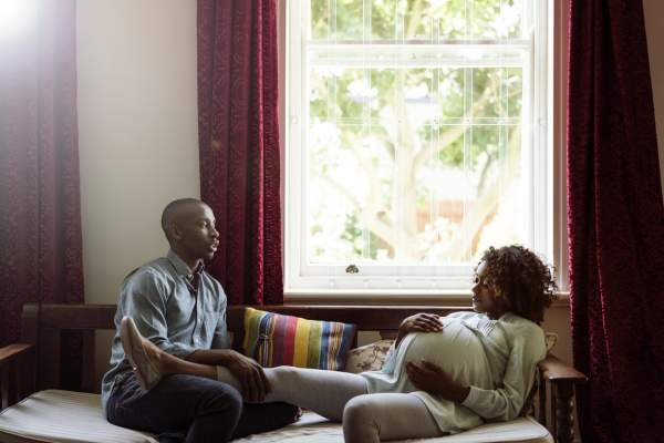 Man talking to pregnant woman in brightly lit home