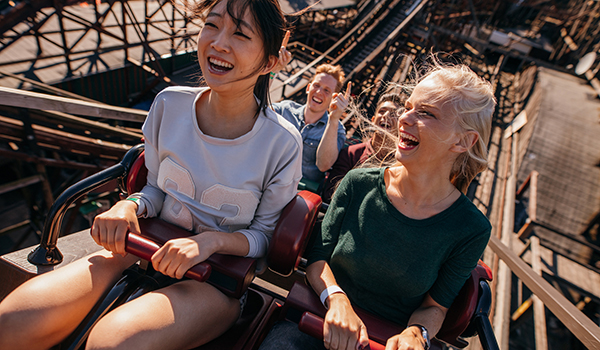 Smiling friends riding a roller coaster