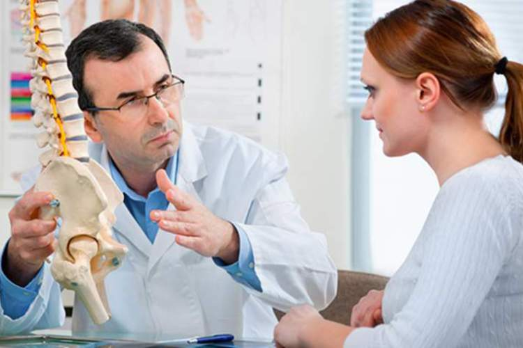 Doctor explaining ankylosing spondylitis to woman.