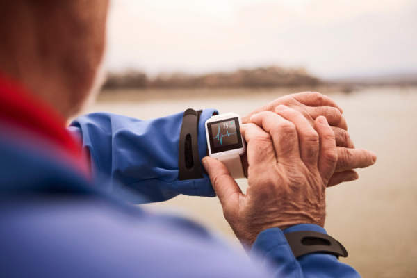 senior man looking at heart rate on fitness watch