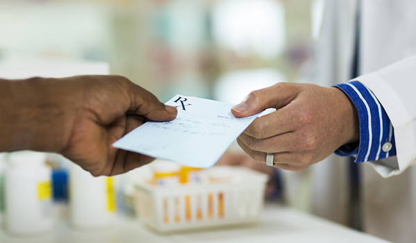 Person of color handing prescription to pharmacist.