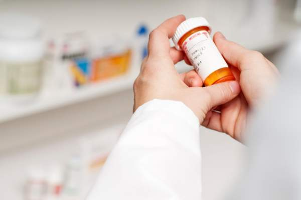 Pharmacist examining a bottle of prescription medicine