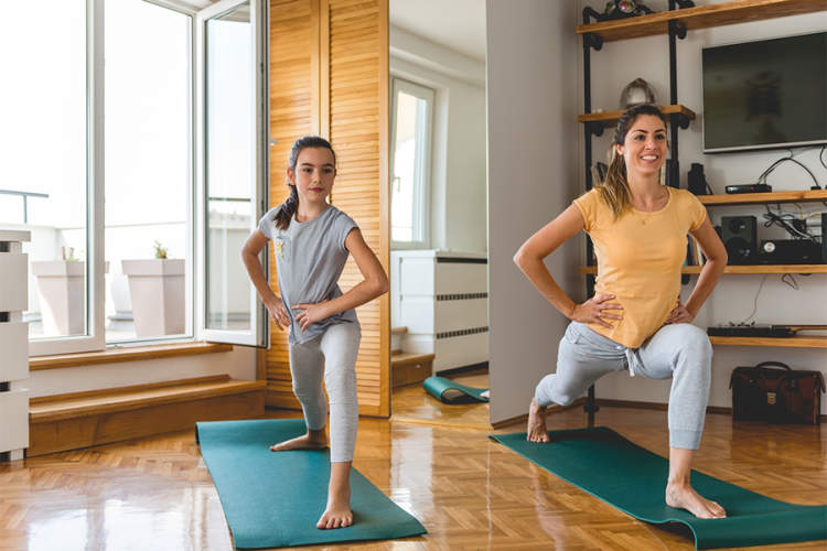 Mother and daughter doing yoga at home.