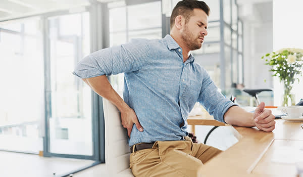 Man sitting in an office with lower back pain.