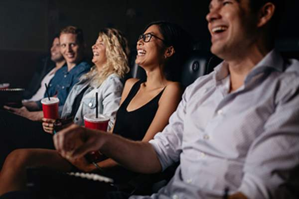 Group of people laughing in a movie theater.