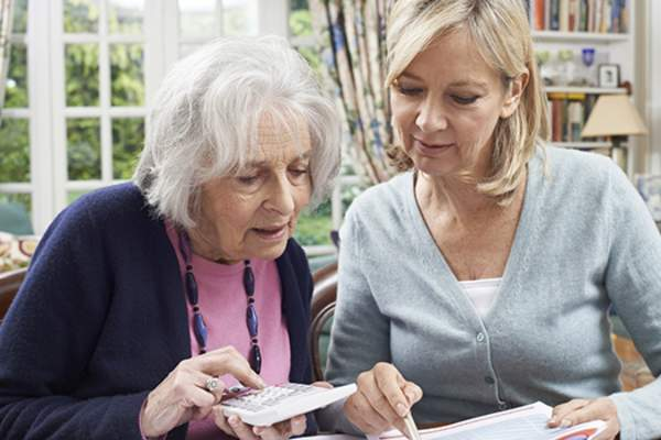 Adult woman helping a senior woman with finances.