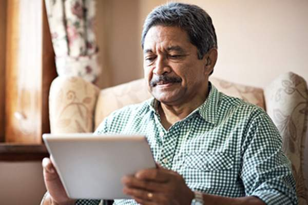 Hispanic senior man on tablet on couch at home.