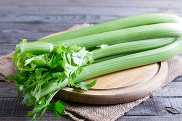 Celery stalks on a cutting board.