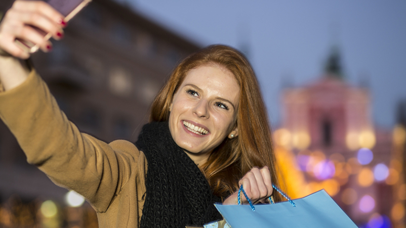 Happy woman taking a selfie while out shopping.