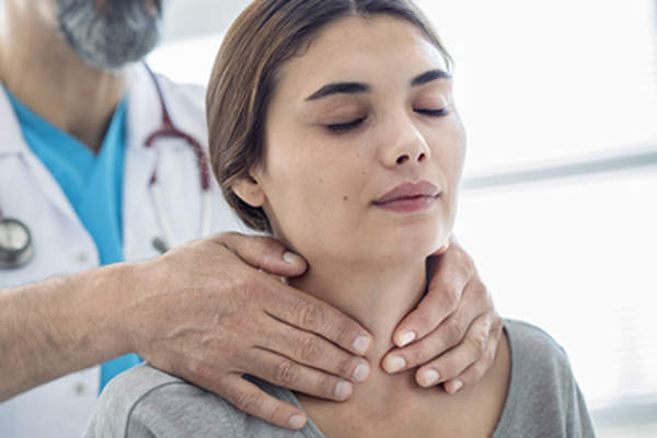 Doctor examining female patient's neck.