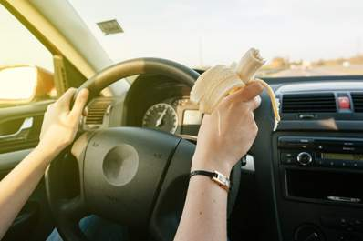 Woman eating a banana while driving image.