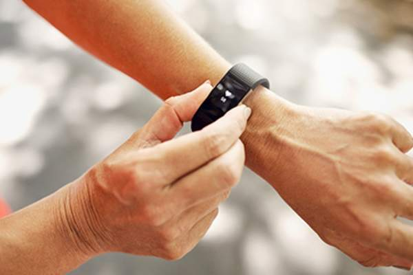 Woman setting fitness tracker on arm.