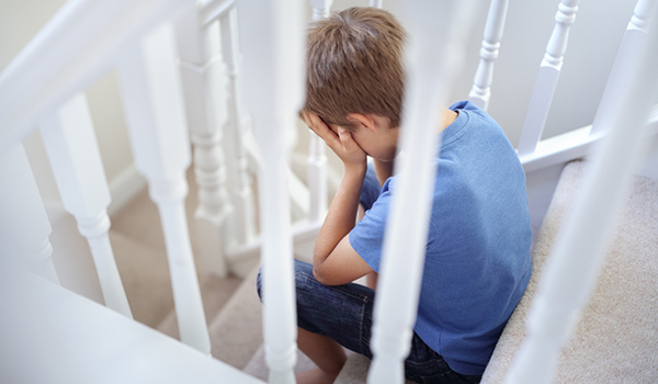 Young boy, upset, sitting on stairs.