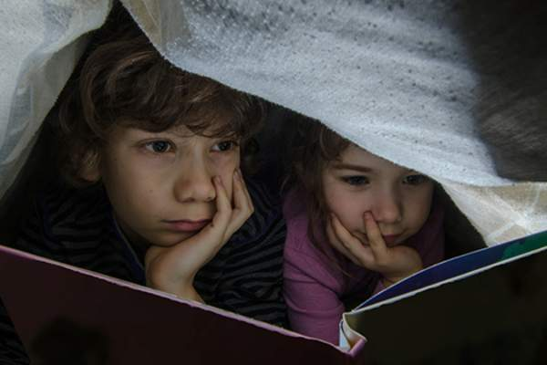 Children reading under a blanket image.