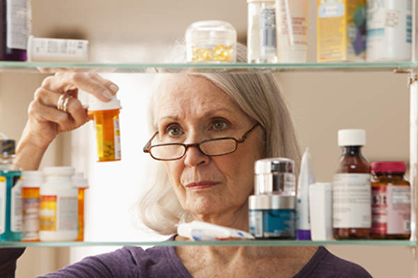 Woman looking at a pill bottle from her medicine cabinet.