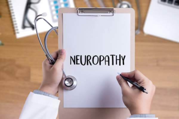 Doctor spelling out neuropathy on clipboard.
