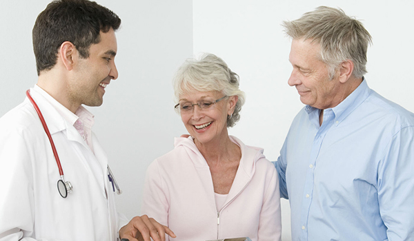 Couple going over paperwork with doctor