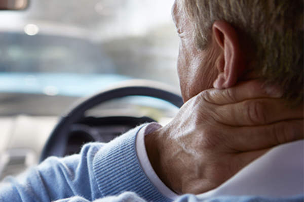 Man with sore neck while driving.
