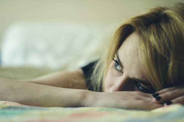 Woman laying in bed unhappy