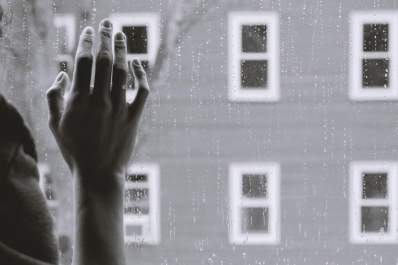 black and white photo of hand against window in the rain
