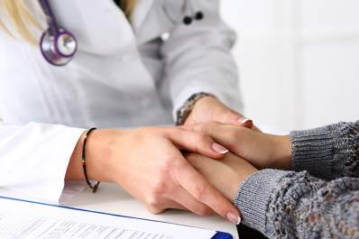 Doctor holding a female patient's hands.