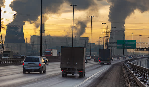 Air pollution from factory with cars on road