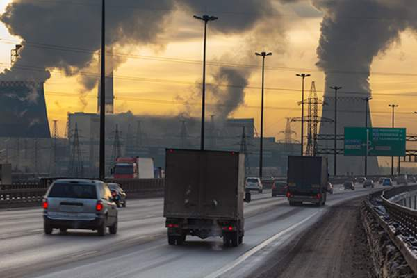 Cars and trucks on road with air pollution.