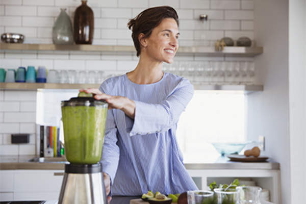 Smiling woman making green smoothies in blender.