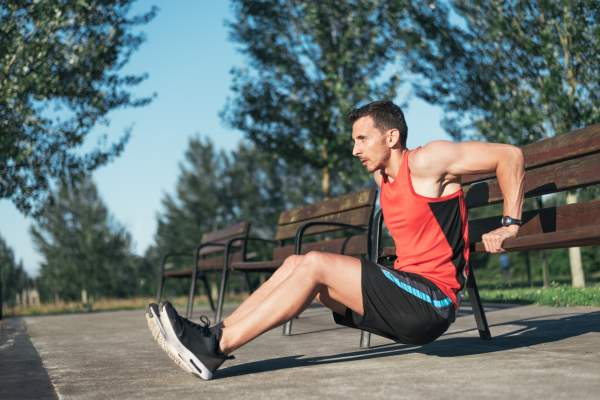 Fitness man doing bench triceps dips outdoors while working out