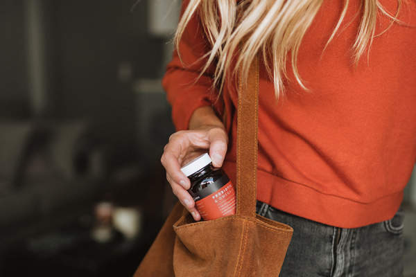 Woman pulling supplement out of bag