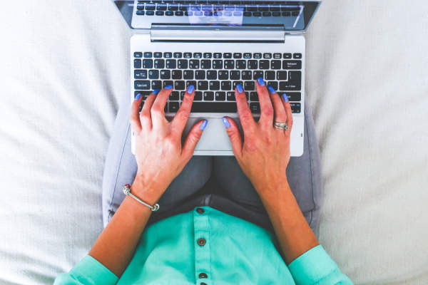 woman sitting on bed typing on laptop