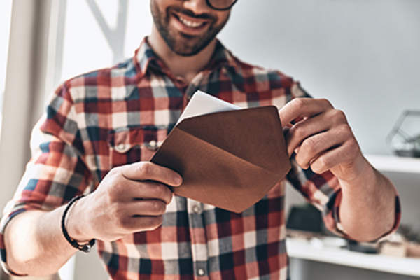 Man putting a letter in an envelope.