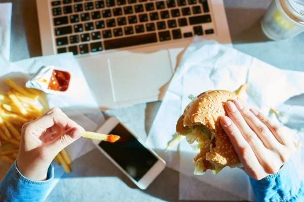 woman eating fast food at desk