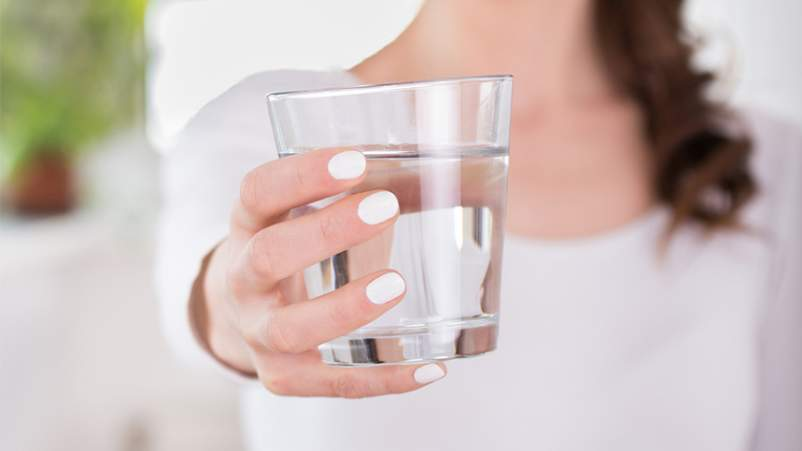 Woman holding a glass of water.