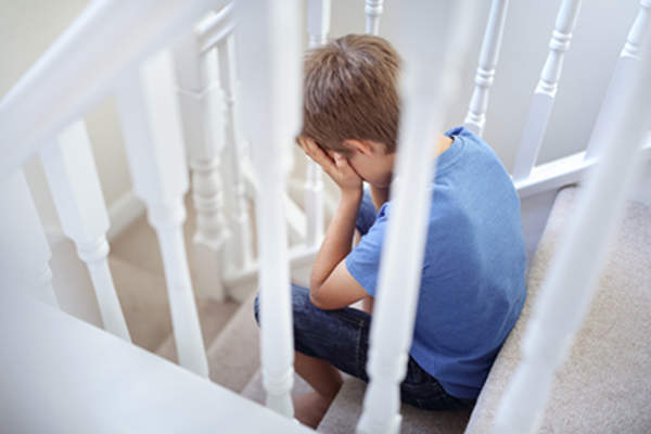 Traumatized little boy crying on the stairs.