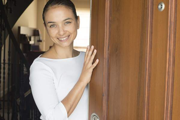 woman opening front door image
