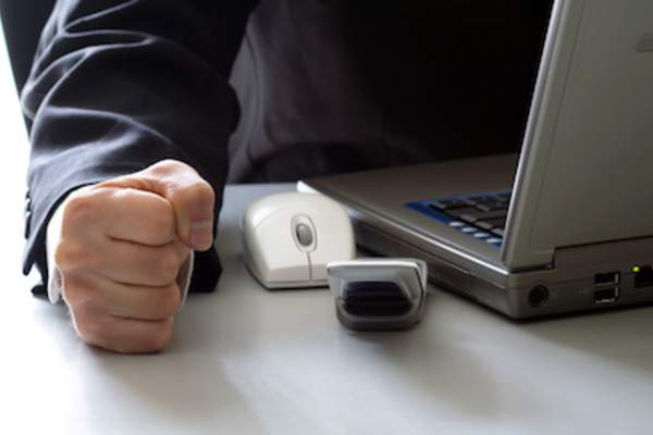Person at computer with a hand clenched into a fist